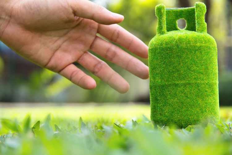 Close-up of hand holding green gas cylinder
