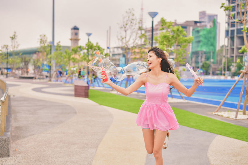 Architecture Arms Outstretched Arms Raised City Day Fashion Focus On Foreground Full Length Girls Hairstyle Human Arm Incidental People Leisure Activity Lifestyles Limb Motion Nature One Person Outdoors Real People Women Young Adult