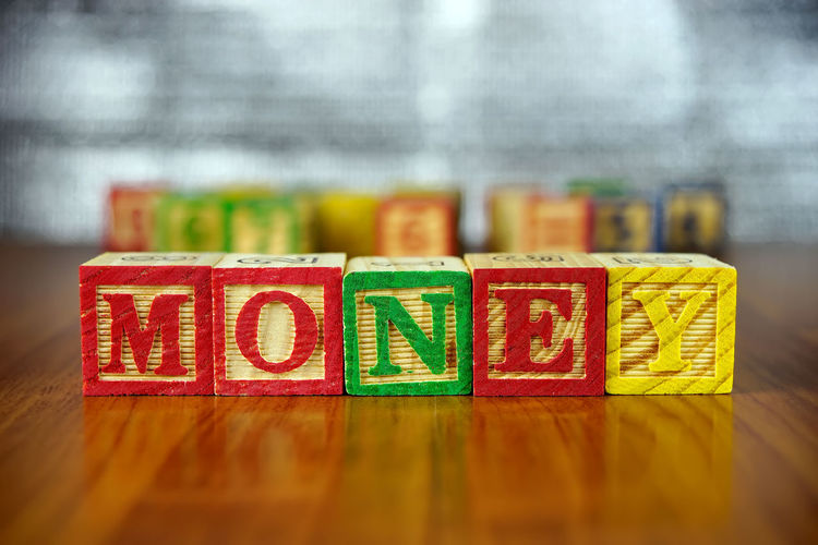 Word MONEY is spelled using the alphabetical blocks on wooden table. Alphabets Collection Focus On Foreground Green Color In A Row Money Multi Colored Playing Selective Focus Spelling Text Toys