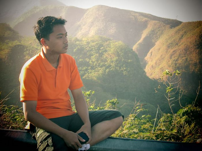 Young man looking away while sitting on mountain