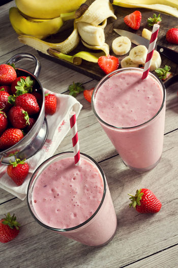 Two Strawberry Banana Yogurt Smoothies or Shakes with Straws and Ingredients on Wooden Table Banana Berries Drinks Ingredients Knife Pink Smoothies Blended Drink Drink Food Frappe Fruit Glass Healthy Eating High Angle View Making Nobody Shake Smoothie Straw Strawberries Strawberry Strawberry Banana Smoothies Table Yogurt