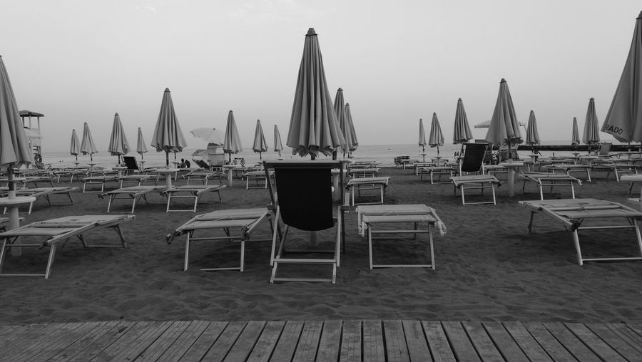 Chairs and parasols at beach against clear sky