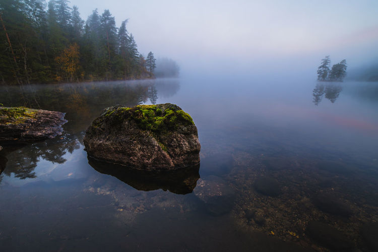 Scenic view of calm lake in foggy weather