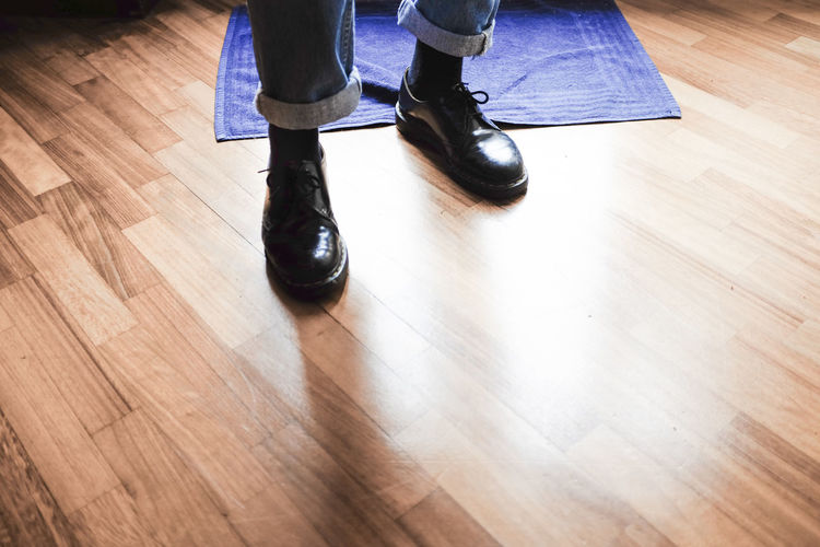 Low section of people standing on hardwood floor