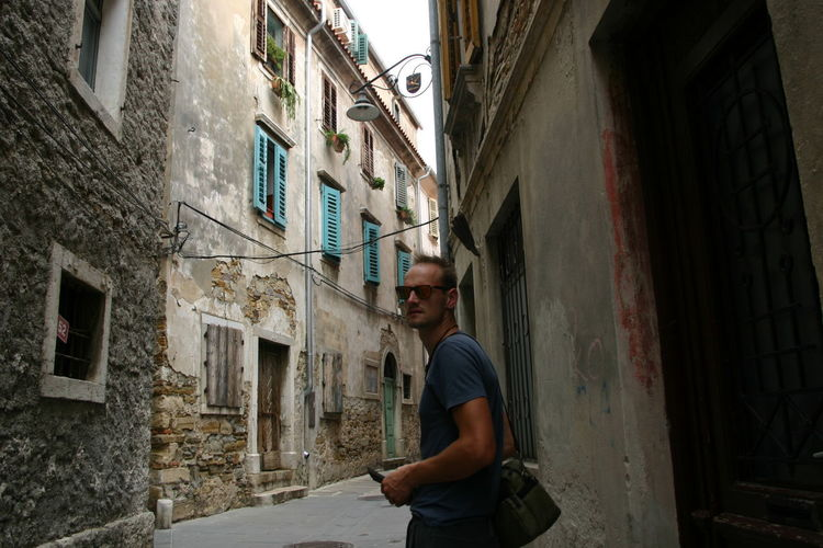 Portrait of man standing in alley amidst buildings