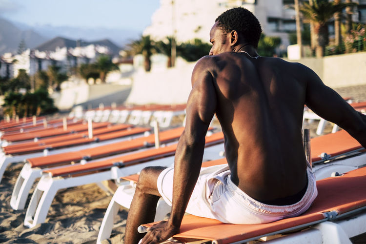 beautiful young black model man sit down on the seats at the beach. Beautiful People Vacations Adult Athlete Back View Of A Man Beach Day Focus On Foreground Healthy Lifestyle Leisure Activity Lifestyles Men Muscular Build Nature One Person Real People Rear View Relaxation Sea Seat Shirtless Sitting Sport Sunlight Three Quarter Length