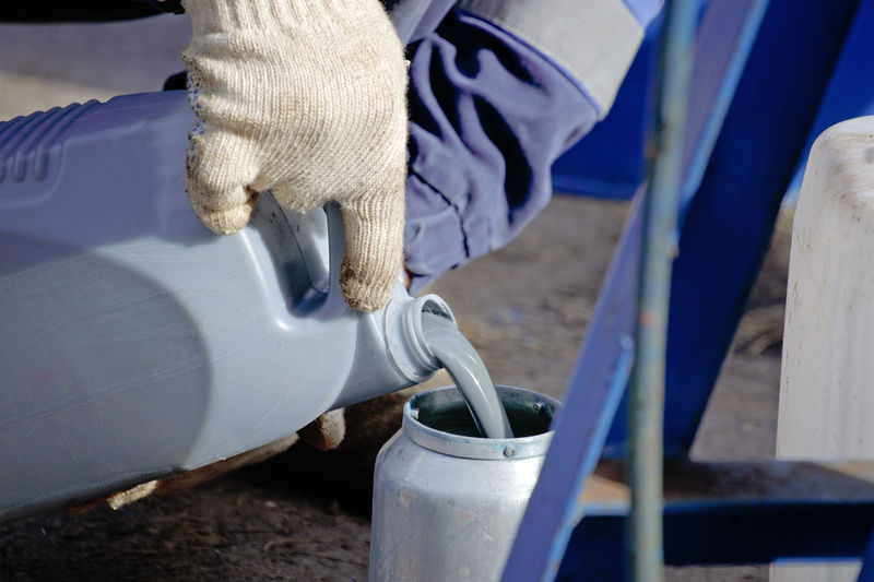 A gloved worker pours gray paint from a canister into a spray gun. preparation for painting works.