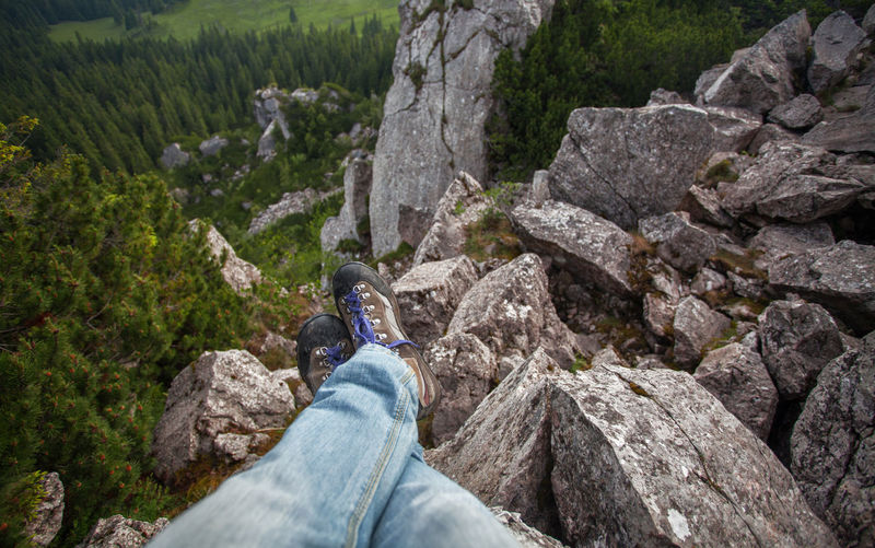 Happy feet in beautiful mountain landscapes. Boots Grass Hiking Man Relaxing Standing View Feet Hike Human Leg Jeans Legs Leisure Activity Low Section Mountain Nature One Person Outdoors Personal Perspective Real People Rock - Object Shoes Valley