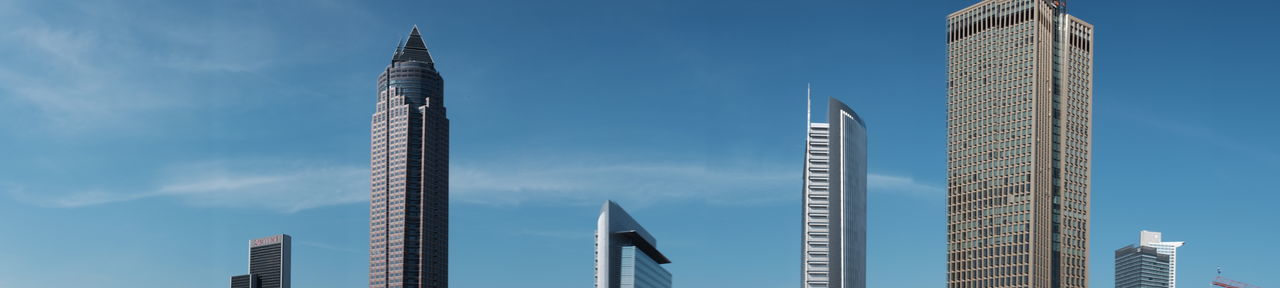 Panoramic view of skyscrapers against blue sky