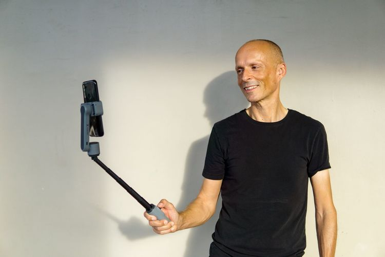 Portrait of man photographing against wall