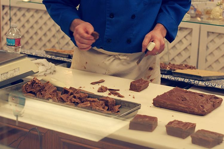 Midsection of chef preparing chocolate fudge at candy store