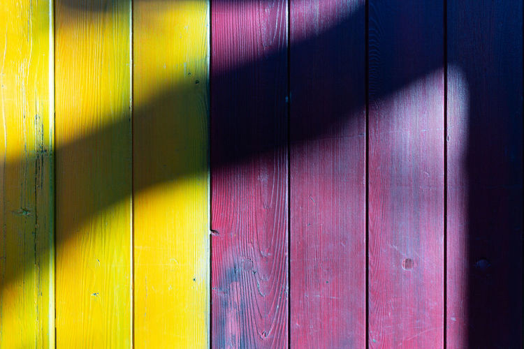 Yellow vs. Purple Wood - Material No People Wall - Building Feature Full Frame Multi Colored Pattern Wood Day Shadow Door Entrance Backgrounds Sunlight Close-up Indoors  Yellow Purple Security Architecture Safety