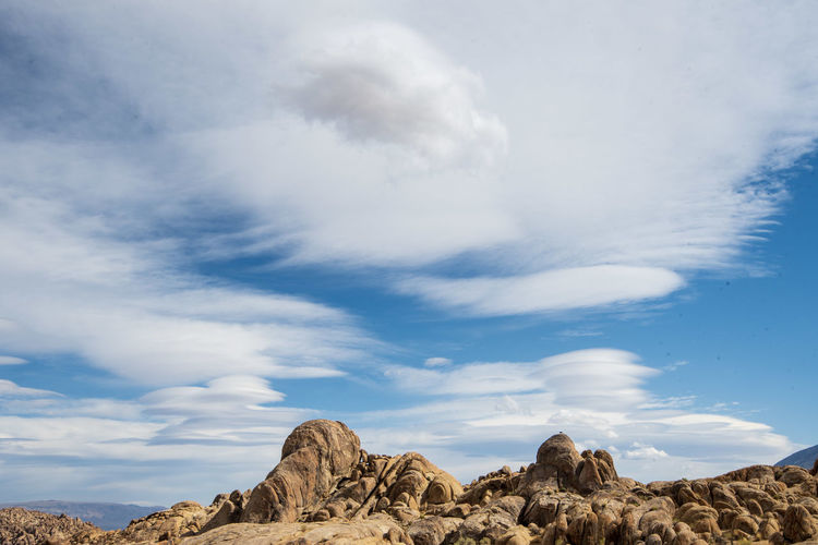Low angle view of rocks against sky in desert with cloud layers above