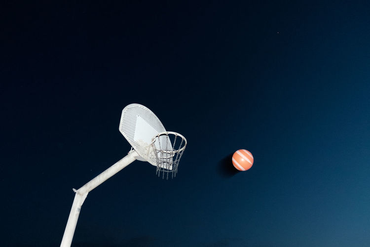Low angle view of basketball hoop against blue background