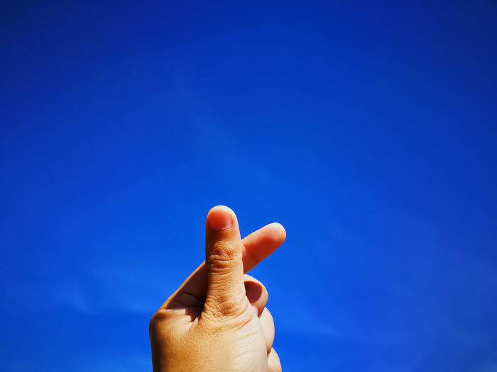 Close-up of cropped hand gesturing against blue sky