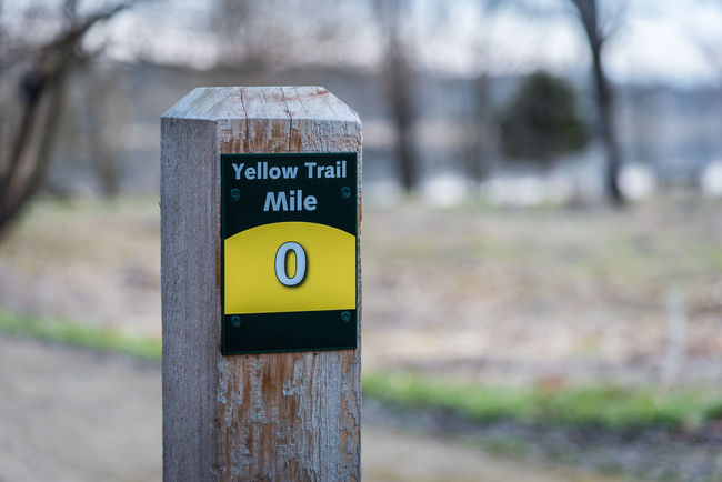 Signpost along forest path mile marker zero 0 Outdoors Trail Marker Signpost Blaze Walking Forest Path No People Selective Focus Yellow Color Woods