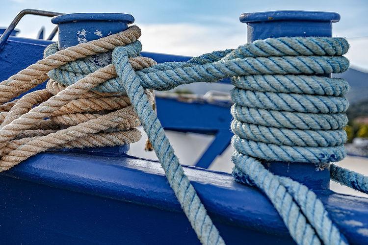 Close-up of ropes tied to bollard