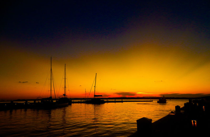 Silhouette sailboats in sea during sunset
