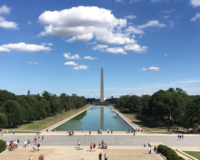 People on street in front of washington monument against sky