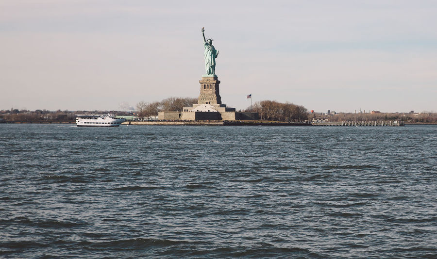 Architecture City City Cultures Day Ferry Freedom New York New York City No People Outdoors Patriotism Sky Staten Island Ferry Statue Statue Of Liberty Travel Destinations Tree Winter