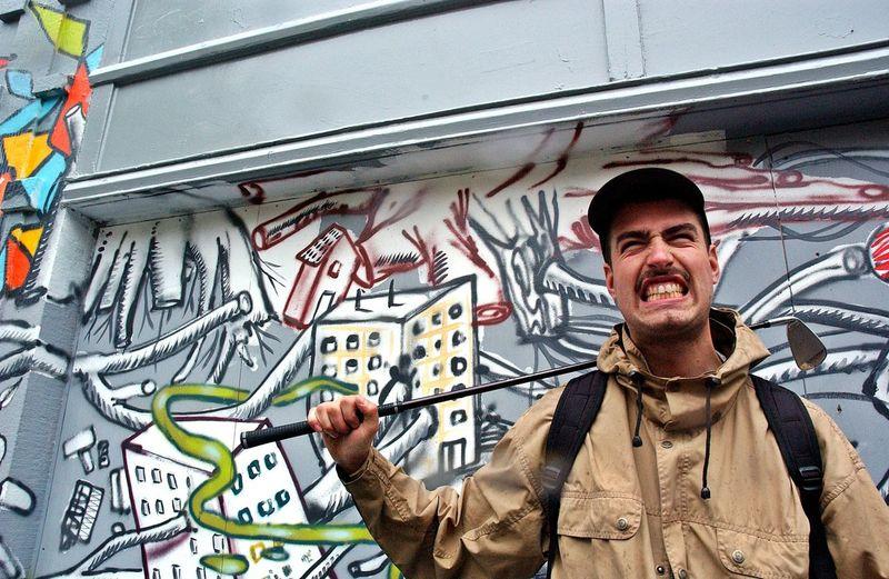 Man Clenching Teeth While Standing Against Graffiti Wall