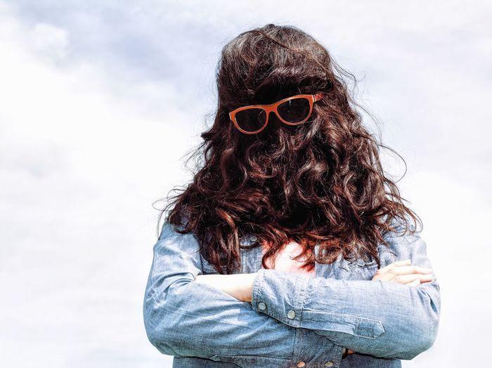Woman Wearing Sunglasses While Covering Face With Hair Against Sky