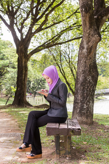 Young woman wearing hijab using mobile phone while sitting in park