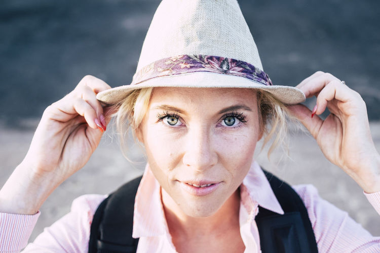 Beautiful european middle age young woman with blue green eyes looking at the camera holding a fashion hat - bright image for attractive people in outdoor leisure activity Portrait Headshot Real People Looking At Camera Front View One Person Hat Women Clothing Focus On Foreground Young Adult Adult Lifestyles Day Young Women Leisure Activity Smiling Hair Outdoors Hairstyle Beautiful Woman Straw Blond Hair Caucasian Traveler