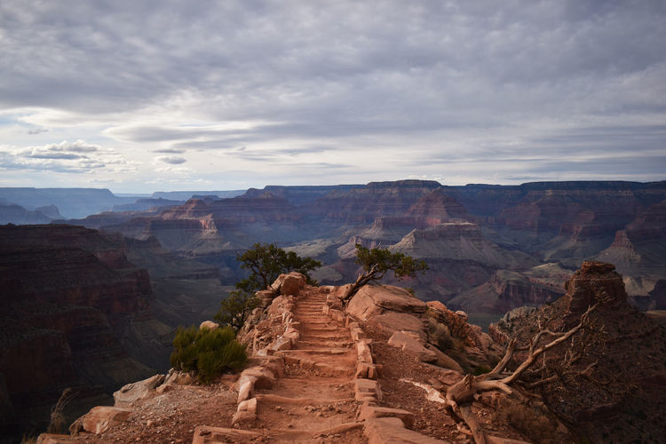 Scenic view of mountain pathway leading to center of frame-  cloudy sky in background.