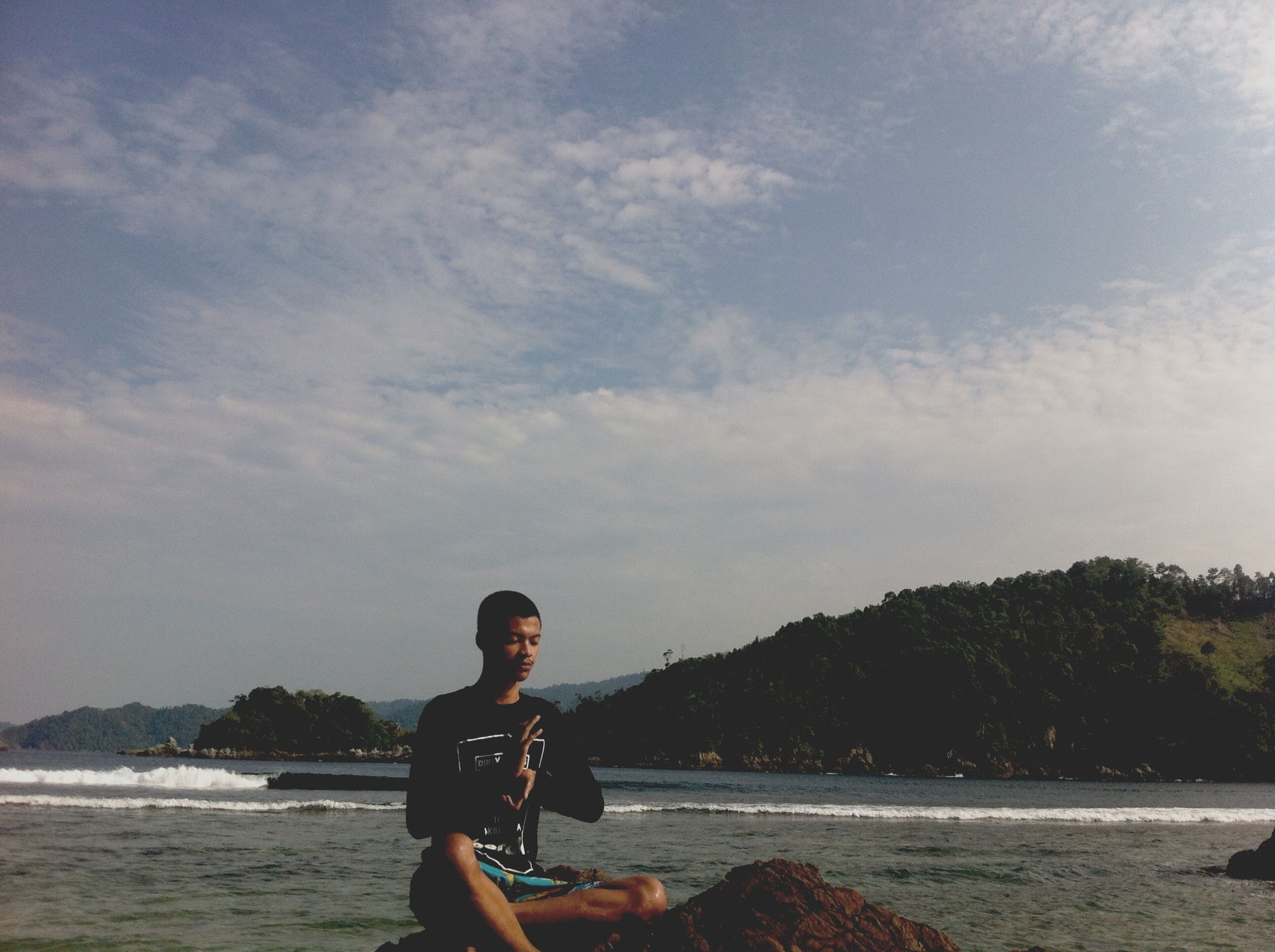 water, lifestyles, leisure activity, sky, young adult, sea, person, casual clothing, tranquility, nature, vacations, beauty in nature, sitting, scenics, three quarter length, beach, tranquil scene, standing