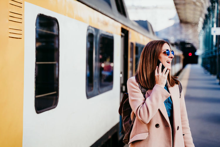 Woman with phone standing by train on railroad station platform
