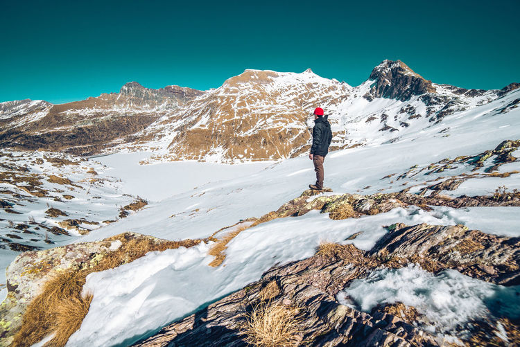 Person walking on snowcapped mountain against sky during winter