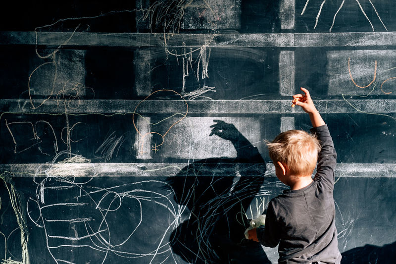 Rear view of boy dancing while looking at shadow on blackboard