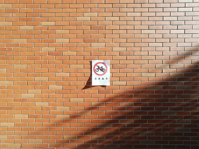 No cycling sign on brick wall on during sunny day
