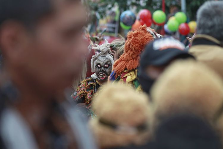 A teenager wears a scary indonesian ghost mask commonly called pocong in a cultural carnival