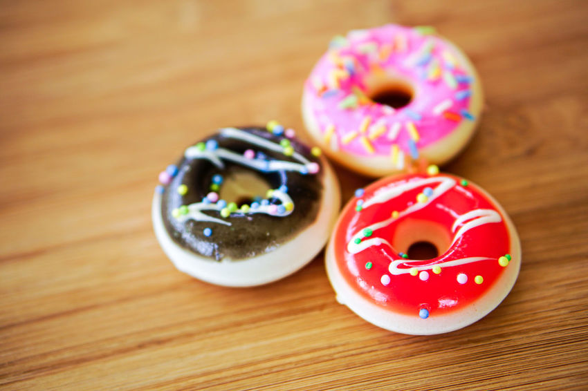 Sweet Food Food Food And Drink Donut Sweet Indoors  Indulgence Icing Group Of Objects Baked Wood - Material No People Close-up Sprinkles Focus On Foreground Multi Colored Dessert Red Table Freshness Snack Temptation