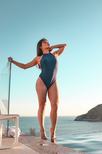 Full length of woman wearing swimwear standing on footpath against sea