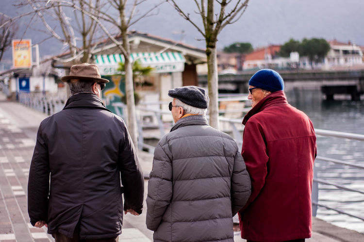 Rear view of friends wearing warm clothing while walking on street in city