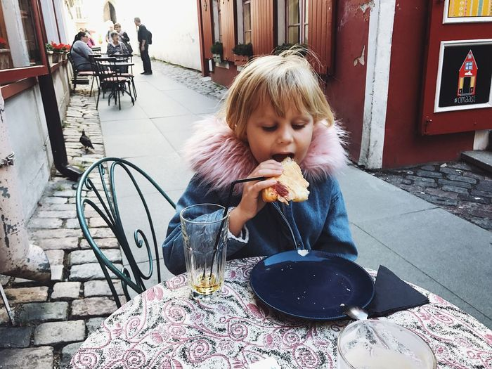 Cute Girl Eating Food At Sidewalk Cafe