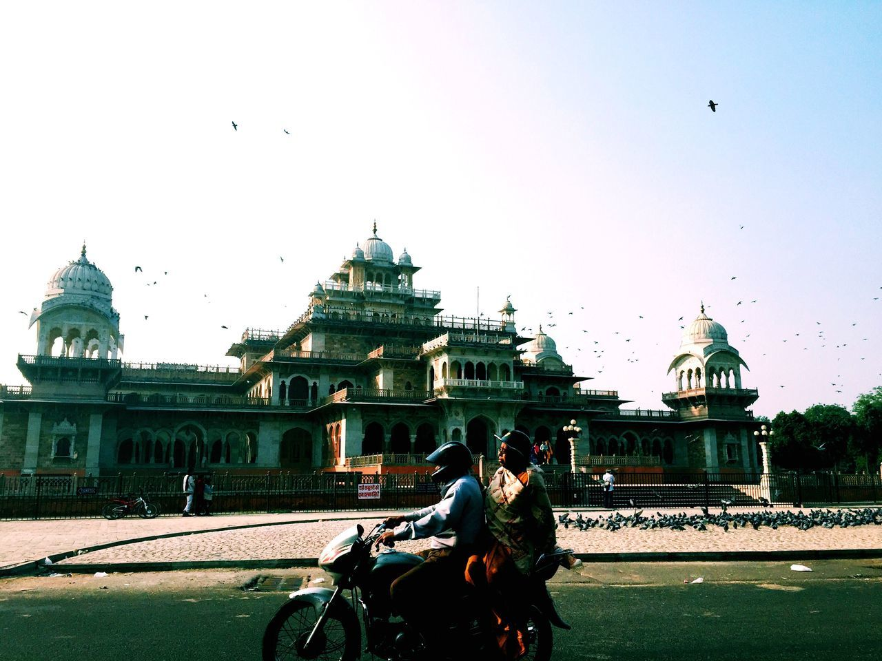 horse, real people, building exterior, horseback riding, built structure, architecture, domestic animals, two animals, dome, day, riding, men, travel destinations, clear sky, horse cart, mammal, place of worship, sky, outdoors, lifestyles, bird, nature, people