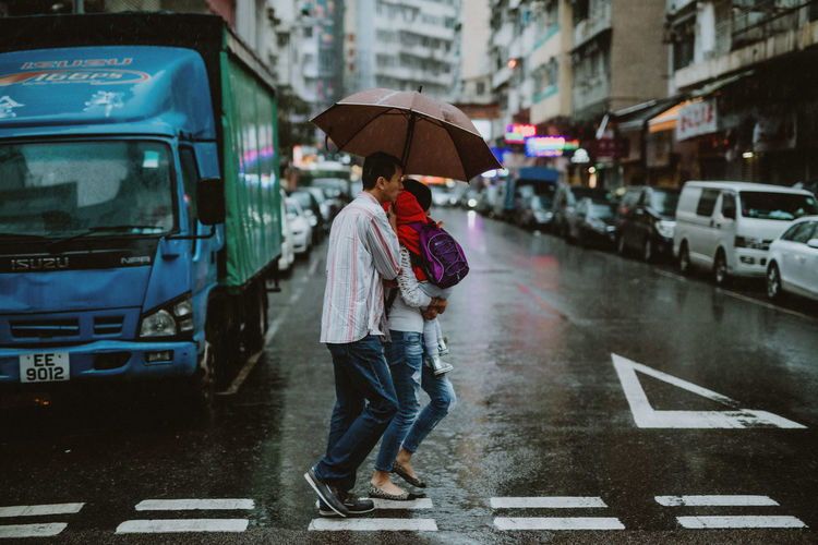 Man standing on wet street in city during monsoon