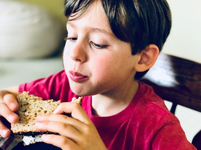 Domestic Child Sandwich At Home Lunch person Headshot Indoors  One Person Real People Focus On Foreground Boys Sitting Food Day Eating Childhood Close-up