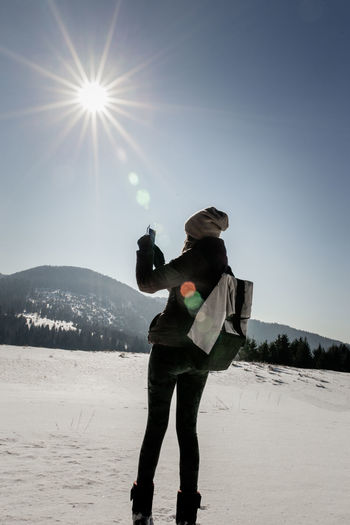 Adventure Clear Sky Cold Temperature Full Length Individuality Lens Flare Nature One Person One Woman Only One Young Woman Only Only Women Outdoors People Photographer Smart Phone Snow Starbucks Sun Sunbeam Sunlight Sunlight Travel Warm Clothing Winter Winter