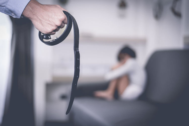 Cropped hand holding belt with girl sitting in background on sofa at home