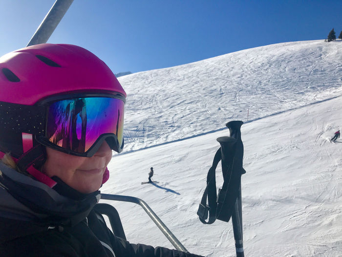 Woman with skiing poles on snowcapped mountain
