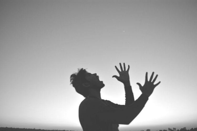 Side view of man screaming while gesturing against sky during sunset