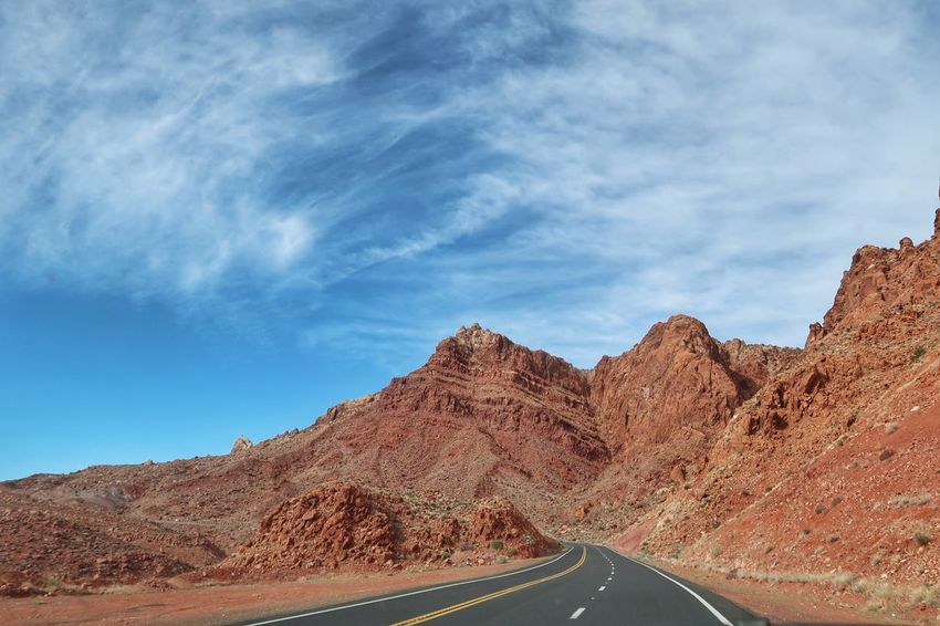 Landscape of road leading to red rocks and hills in Arizona Page Arizona Sky Cloud - Sky Mountain Nature Scenics - Nature Beauty In Nature Day Transportation Mountain Range Tranquil Scene Road No People Environment Non-urban Scene Tranquility Rock Blue Landscape Solid Sunlight