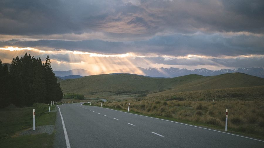 Road by mountains against dramatic sky