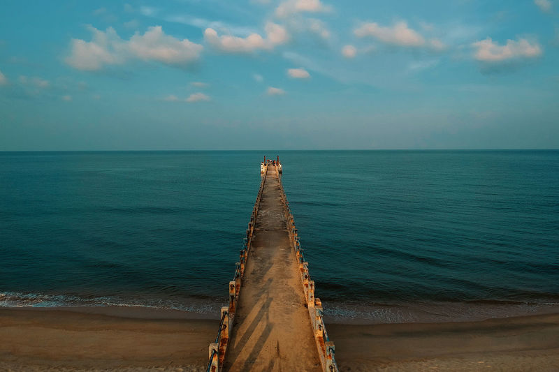 Diminishing perspective of pier over sea against sky during sunset