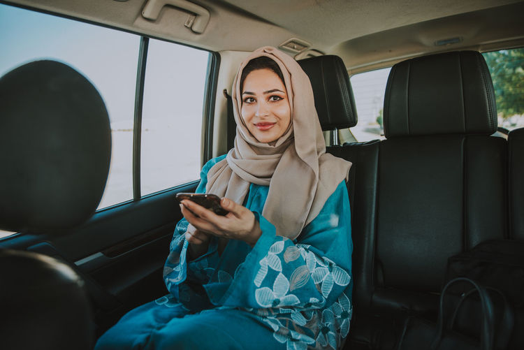 Young smiling woman using phone while sitting in car